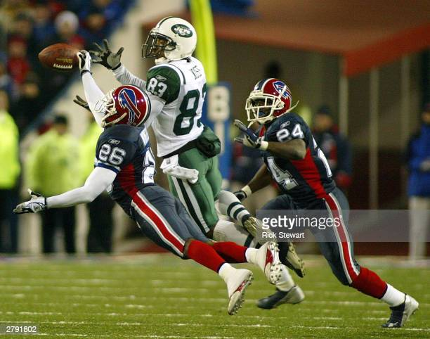 Antoine Winfield of the Buffalo Bills breaks up a pass intended for Santana Moss of the New York Jets as Terrence McGee watches on December 7 2003 at...