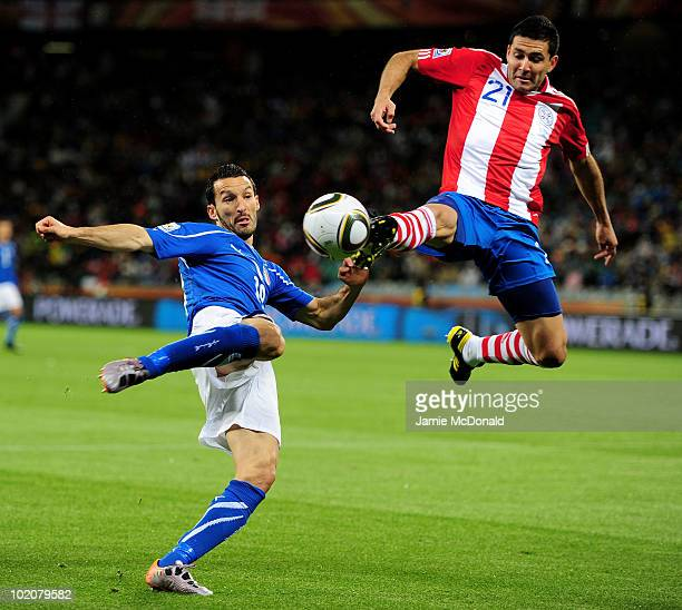 Antolin Alcaraz of Paraguay jumps into a tackle on Gianluca Zambrotta of Italy during the 2010 FIFA World Cup South Africa Group F match between...