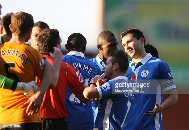 Antolin Alcaraz of Wigan Athletic shrugs his shoulders to Referee Lee Probert after he appeared to spit at Christophe Berra of Wolverhampton Wanderers