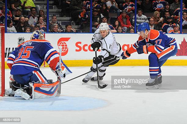 Anton Belov and Viktor Fasth of the Edmonton Oilers stop a shot from Kyle Clifford of the Los Angeles Kings on April 10 2014 at Rexall Place in...