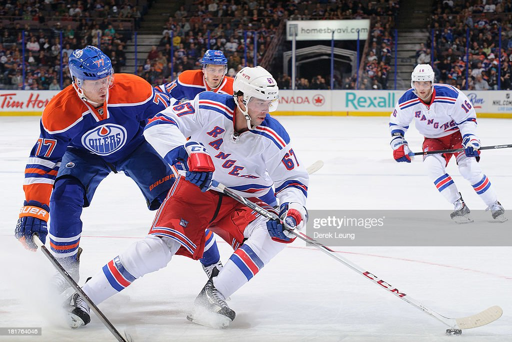 Anton Belov #77 of the Edmonton Oilers tries to check <a gi-track='captionPersonalityLinkClicked' href=/galleries/search?phrase=Benoit+Pouliot&family=editorial&specificpeople=879830 ng-click='$event.stopPropagation()'>Benoit Pouliot</a> #67 of the New York Rangers during a preseason NHL game at Rexall Place on September 24, 2013 in Edmonton, Alberta, Canada.