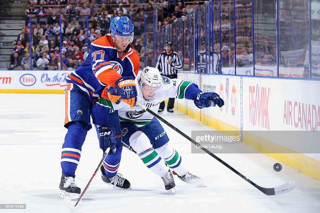 Anton Belov #77 of the Edmonton Oilers tries to check <a gi-track='captionPersonalityLinkClicked' href=/galleries/search?phrase=Hunter+Shinkaruk&family=editorial&specificpeople=7619011 ng-click='$event.stopPropagation()'>Hunter Shinkaruk</a> of the Vancouver Canucks during a preseason NHL game at Rexall Place on September 21, 2013 in Edmonton, Alberta, Canada.