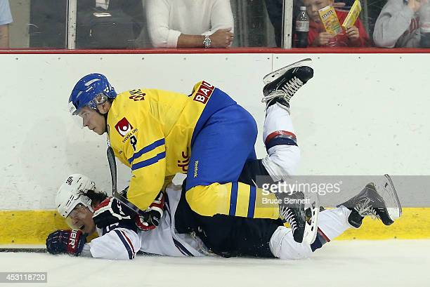 Anton Cederholm of Team Sweden checks Sonny Milano of USA White during the 2014 USA Hockey Junior Evaluation Camp at the Lake Placid Olympic Center...