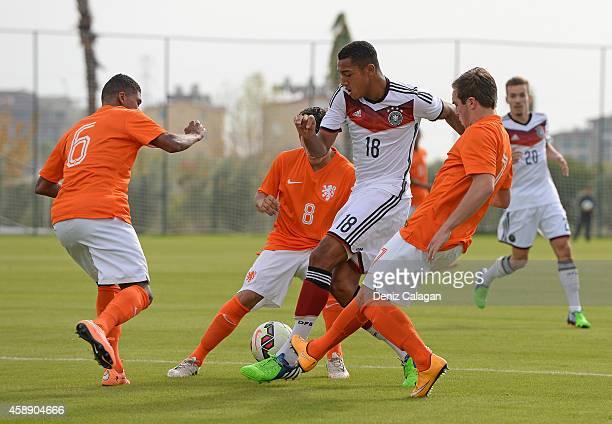 Anton Donkor of Germany challenges Laros Duarte Gustavo Harner and Martijn Berden of Netherlands during the international friendly match between U18...