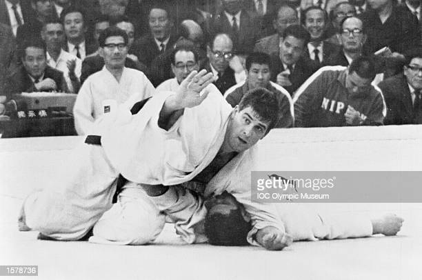 Anton Geesink of the Netherlands holds down Akio Kaminaga of Japan shortly before winning the open judo category at the 1964 Olympic Games in Tokyo...