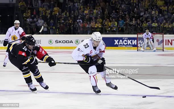 Anton Karlsson competes with Andreas Driendl during the Champions Hockey League group stage game between Krefeld Pinguine and Skelleftea AIK on...