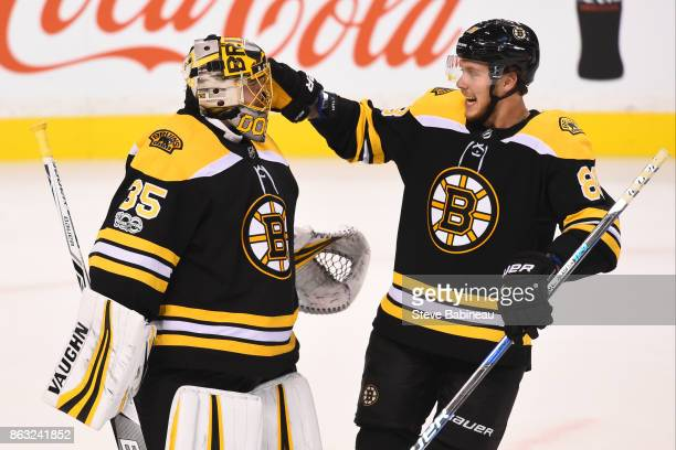 Anton Khudobin and David Pastrnak of the Boston Bruins celebrate a win against the Vancouver Canucks at the TD Garden on October 19 2017 in Boston...