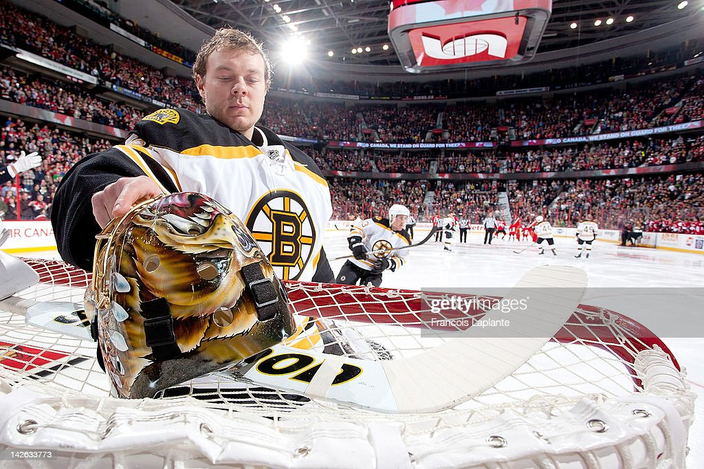 Anton Khudobin #35 of the Boston Bruins grabs his mask on the net prior to a game against the Ottawa Senators at Scotiabank Place on April 5, 2012 in Ottawa, Ontario, Canada.