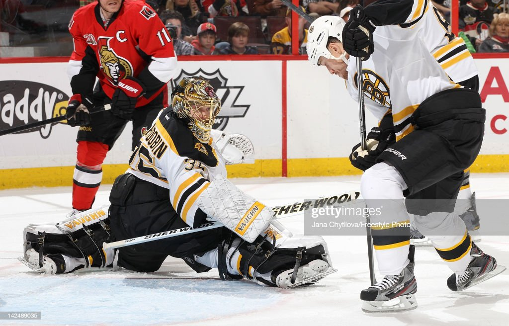 <a gi-track='captionPersonalityLinkClicked' href=/galleries/search?phrase=Anton+Khudobin&family=editorial&specificpeople=722106 ng-click='$event.stopPropagation()'>Anton Khudobin</a> #35 of the Boston Bruins makes one of forty-four saves as teammate <a gi-track='captionPersonalityLinkClicked' href=/galleries/search?phrase=Joe+Corvo&family=editorial&specificpeople=206339 ng-click='$event.stopPropagation()'>Joe Corvo</a> #14 corals the rebound during an NHL game against the Ottawa Senators at Scotiabank Place on April 5, 2012 in Ottawa, Ontario, Canada.