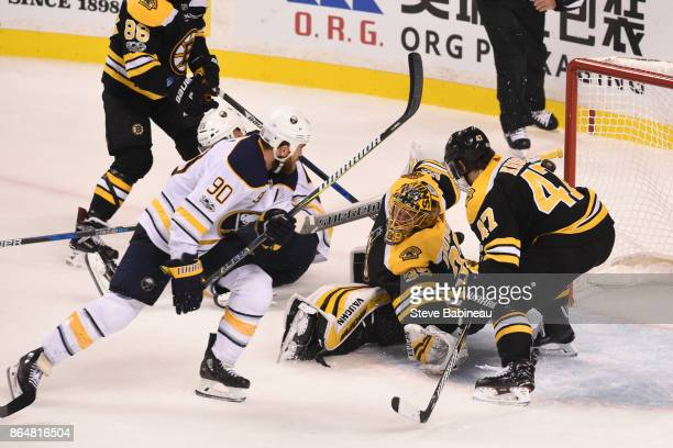Anton Khudobin of the Boston Bruins reaches for the puck against Ryan O'Reilly of the Buffalo Sabres at the TD Garden on October 21 2017 in Boston...