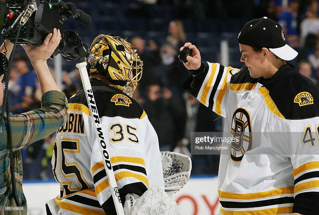 <a gi-track='captionPersonalityLinkClicked' href=/galleries/search?phrase=Anton+Khudobin&family=editorial&specificpeople=722106 ng-click='$event.stopPropagation()'>Anton Khudobin</a> #35 of the Boston Bruins receives the game puck from teammate <a gi-track='captionPersonalityLinkClicked' href=/galleries/search?phrase=Tuukka+Rask&family=editorial&specificpeople=716723 ng-click='$event.stopPropagation()'>Tuukka Rask</a> #40 after his 2-0 shutout against the Buffalo Sabres on March 31, 2013 at the First Niagara Center in Buffalo, New York.