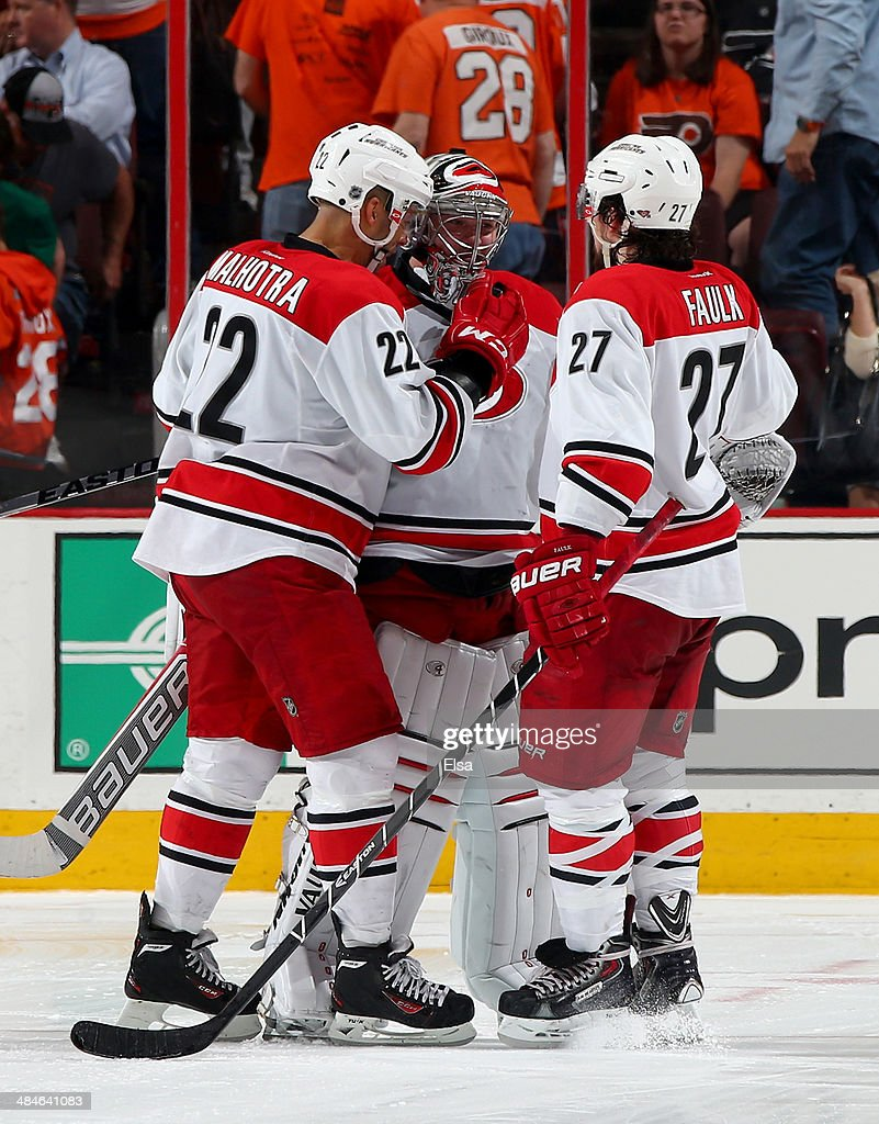 <a gi-track='captionPersonalityLinkClicked' href=/galleries/search?phrase=Anton+Khudobin&family=editorial&specificpeople=722106 ng-click='$event.stopPropagation()'>Anton Khudobin</a> #31 of the Carolina Hurricanes celebrates the win with teammates <a gi-track='captionPersonalityLinkClicked' href=/galleries/search?phrase=Manny+Malhotra&family=editorial&specificpeople=204479 ng-click='$event.stopPropagation()'>Manny Malhotra</a> #22 and Justin Faulk #27 after the game against the Philadelphia Flyers at Wells Fargo Center on April 13, 2014 in Philadelphia, Pennsylvania.The Carolina Hurricanes defeated the Philadelphia Flyers 6-5 in an overtime shootout.