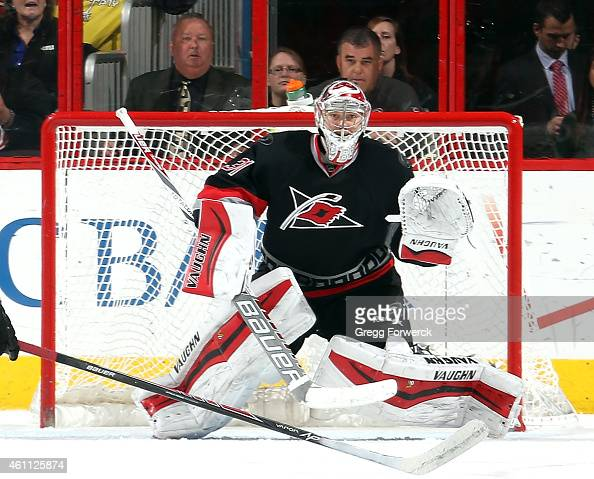Anton Khudobin of the Carolina Hurricanes keeps his eye on the puck as he crouches in the crease to make a glove save during their NHL game against...