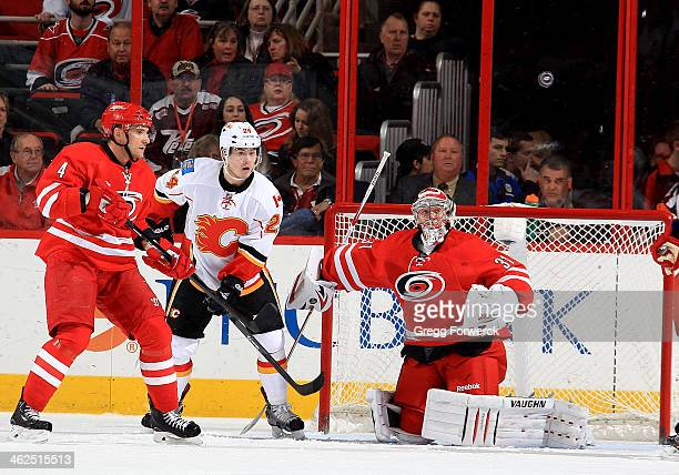 Anton Khudobin of the Carolina Hurricanes keeps his eye on the puck as teammate Andrej Sekera and Jiri Hudler of the Calgary Flames battle by the net...