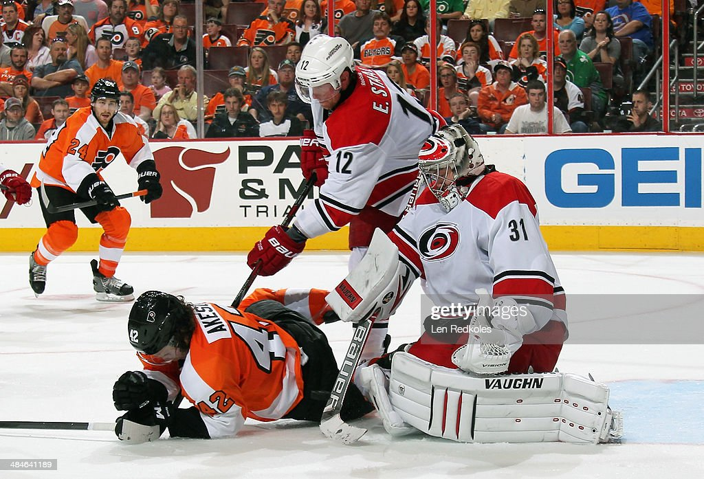 Anton Khudobin #31 of the Carolina Hurricanes makes a save as teammate Eric Staal #12 defends against Jason Akeson #42 of the Philadelphia Flyers on April 13, 2014 at the Wells Fargo Center in Philadelphia, Pennsylvania.