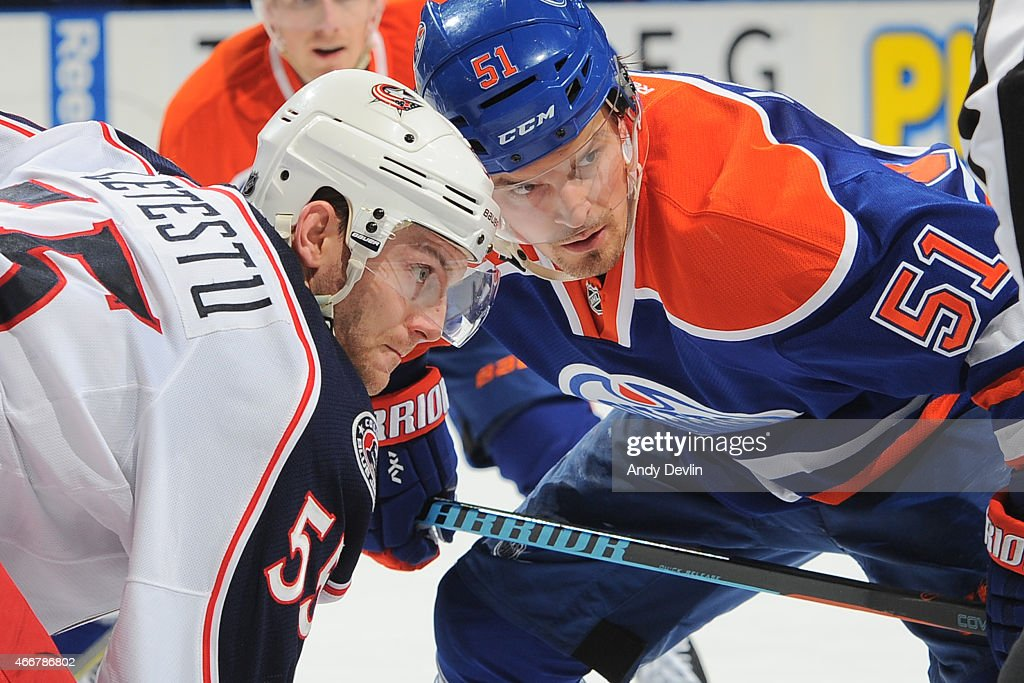 Anton Lander of the Edmonton Oilers lines up to take a face off against Mark Letestu of the Columbus Blue Jackets on March 18 2015 at Rexall Place in...