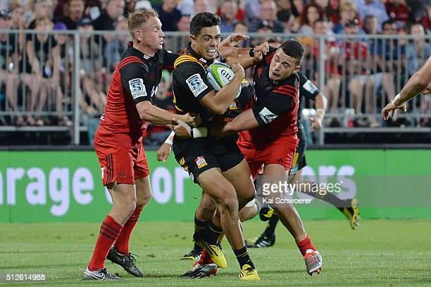 Anton LienertBrown of the Chiefs is tackled by Andy Ellis and David Havili of the Crusaders during the round one Super Rugby match between the...