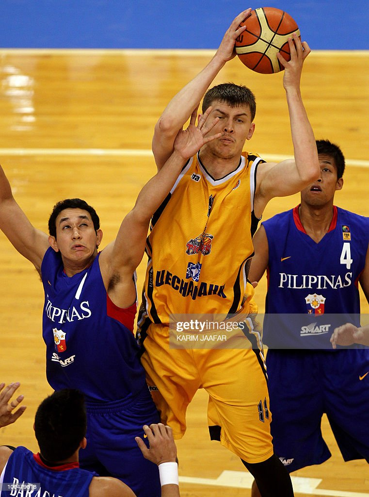 Anton Ponomarev (C) of Kazakhstan's Astana Tigers club fights for the ball with Dylan Simon Ababou (L) and Andy Mark Barocca (R) of Philippines' Smart Gilas club tries to stop him during their 21st FIBA Asia Champions Cup basketball match at the Al-Gharafa indoors stadium in Doha on May 24, 2010.
