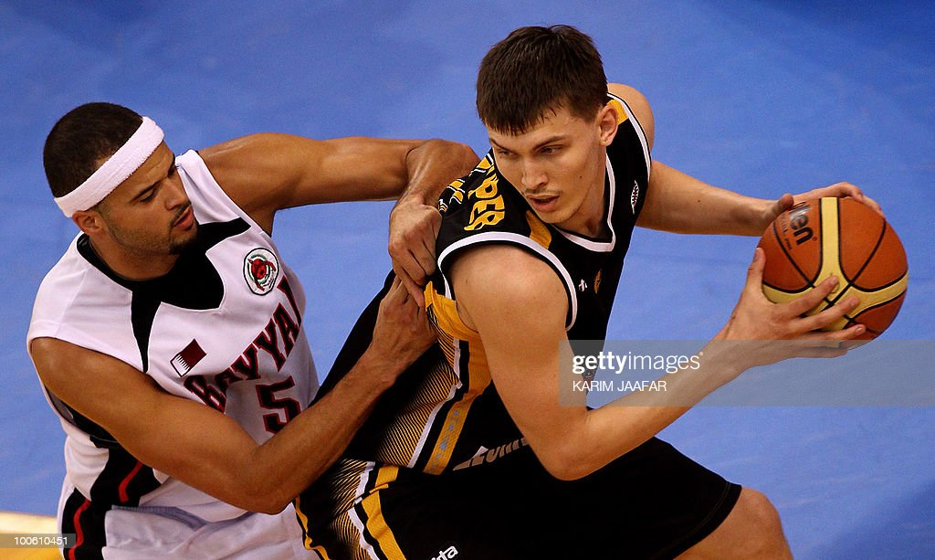 Anton Ponomarev of Kazakhstan's Astana Tigers (R) is challenged by Michael D'Andre Fey of Qatar's Al-Rayyan during their 21st FIBA Asia Champions Cup basketball match at Al-Gharafa Indoor Stadium in Doha on May 25, 2010.