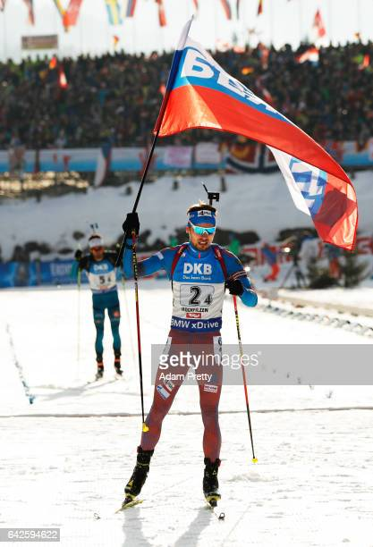 Anton Shipulin of Russia crosses the line first for victory over Martin Fourcade and team France during the Men's 4x 75km relay competition of the...