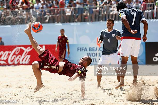 Anton Shkarin of Russia attempts an scissor kick on goal as Edgar Barreto of Paraguay lepas to stop the ball during the Group D FIFA Beach Soccer...