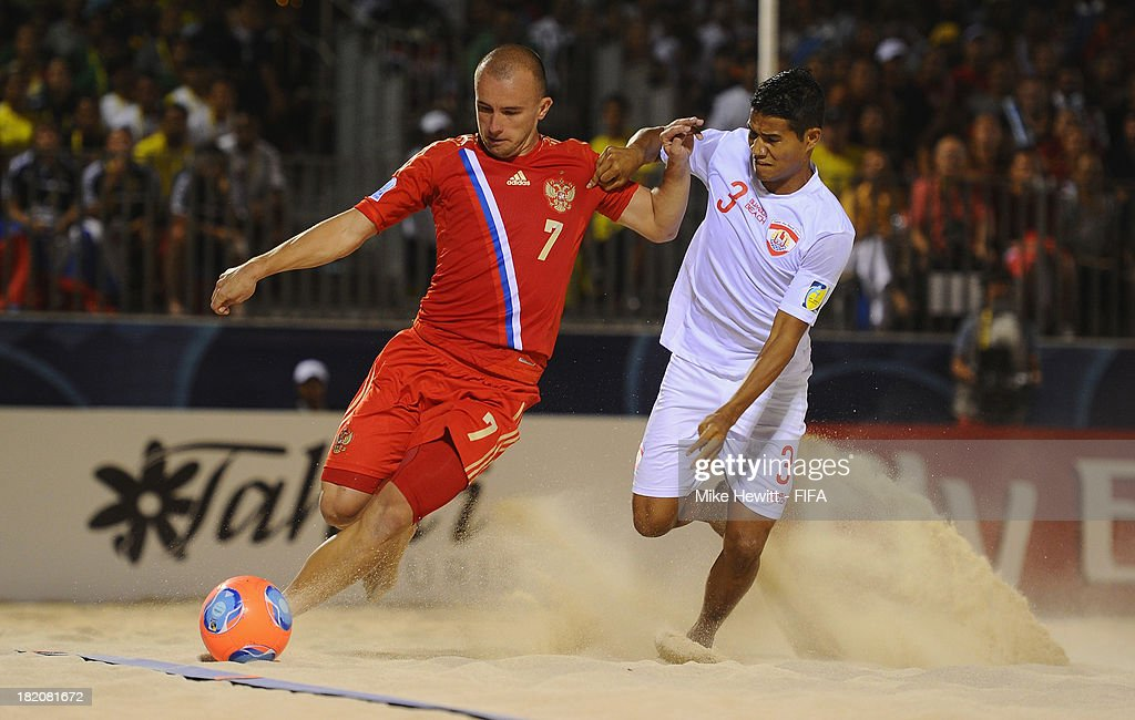 Anton Shkarin of Russia is challenged by Marama Amau of Tahiti during the FIFA Beach Soccer World Cup Tahiti 2013 Semi Final match between Russia and Tahiti at the Tahua To'ata Stadium on September 27, 2013 in Papeete, French Polynesia.