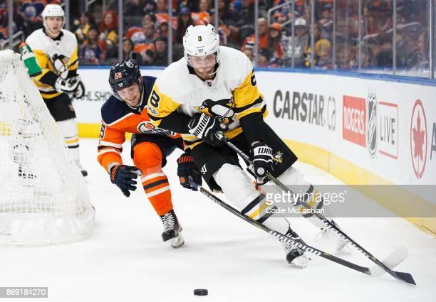 Anton Slepyshev of the Edmonton Oilers battles against Brian Dumoulin of the Pittsburgh Penguins at Rogers Place on November 1 2017 in Edmonton Canada