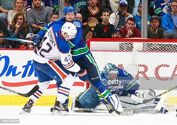 Anton Slepyshev of the Edmonton Oilers battles Alexander Edler of the Vancouver Canucks for position in front of Ryan Miller of the Canucks during...