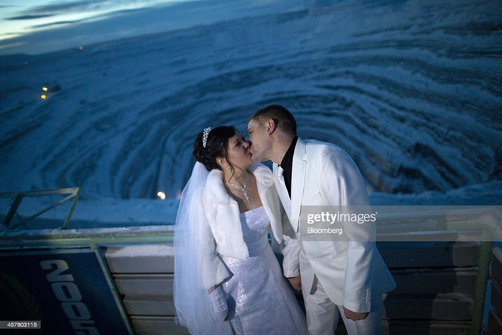 Anton Stolyarov, the bridegroom, right, and Elena Mustafina, the bride, kiss as they pose for wedding photographs at a viewing point beside the giant open pit diamond mine operated by OAO Alrosa in Udachny, Sakha Republic, Russia, on Thursday, Dec. 12, 2013. Russia plans to maintain control of Mirny-based Alrosa, which produces a quarter of the world's diamonds by value and more rough diamonds than De Beers by carat. Photographer: Andrey Rudakov/Bloomberg via Getty Images