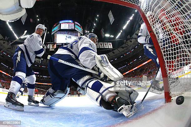 Anton Stralman and Andrei Vasilevskiy of the Tampa Bay Lightning watch a shot by Jonathan Toews of the Chicago Blackhawks cross the line in the...