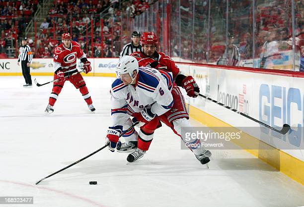 Anton Stralman of the New York Rangers is defended by Chad LaRose of the Carolina Hurricanes during their NHL game at PNC Arena on April 25 2013 in...