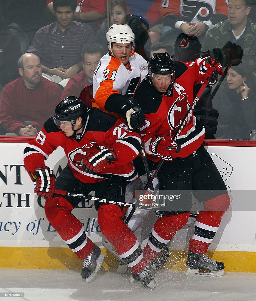 Anton Volchenkov #28 and Ilya Kovalchuk #17 of the New Jersey Devils combine to hit James van Riemsdyk #21 of the Philadelphia Flyers at the Prudential Center on January 6, 2011 in Newark, New Jersey.