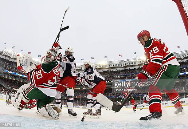Anton Volchenkov and Martin Brodeur of the New Jersey Devils defend against Benoit Pouliot and Derick Brassard of the New York Rangers in the second...