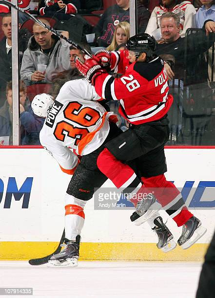 Anton Volchenkov of the New Jersey Devils climbs the back of Darroll Powe of the Philadelphia Flyers during the game at the Prudential Center on...