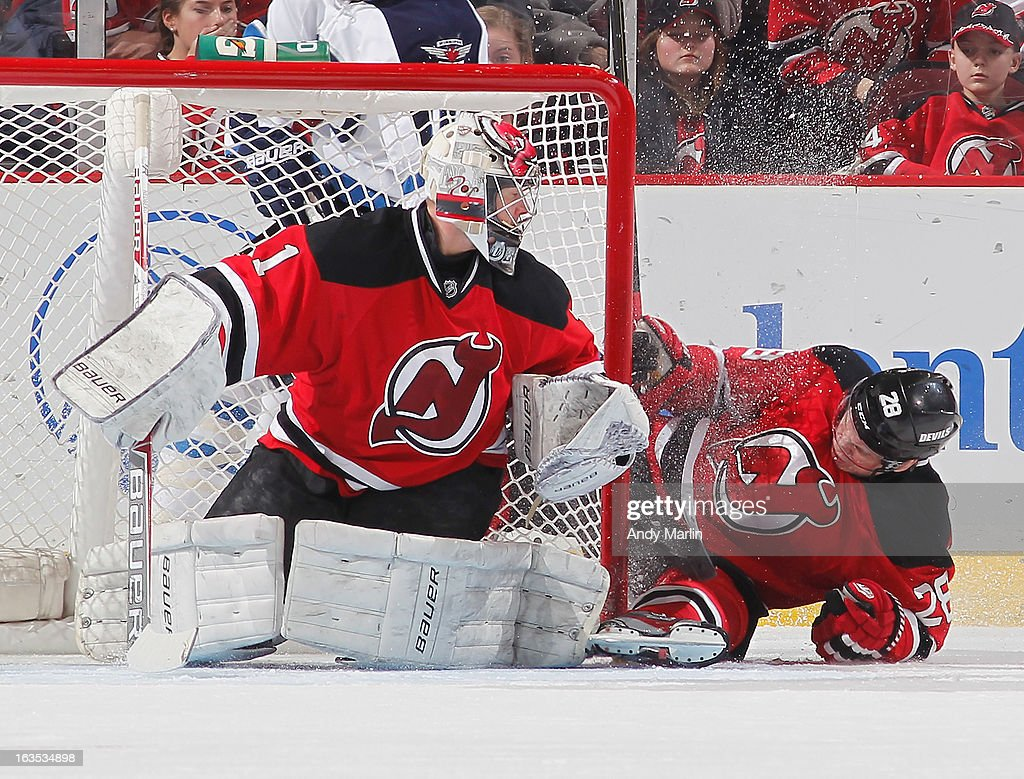 Anton Volchenkov #28 of the New Jersey Devils goes sliding into the post next to goaltender Johan Hedberg #1 against the Winnipeg Jets during the game at the Prudential Center on March 10, 2013 in Newark, New Jersey.
