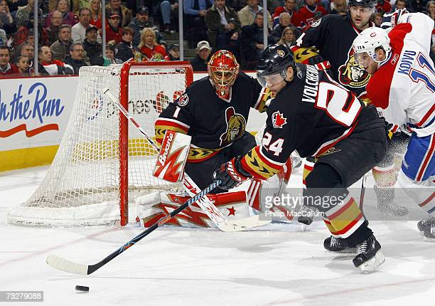 Anton Volchenkov of the Ottawa Senators tries to clear the puck from out front of his net while being chased by Saku Koivu of the Montreal Canadiens...