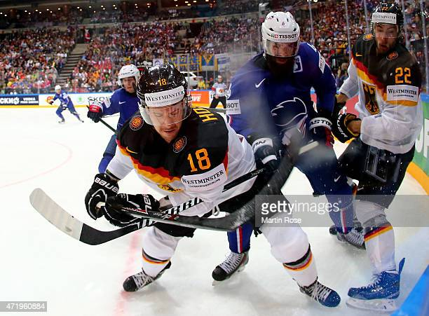 Antonin Manavian of France and Thomas Oppenheimer of Germnay battle for the puck during the IIHF World Championship group A match between France and...