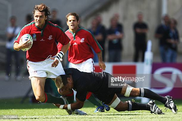 Antonio Aguilar of Portugal is stopped by Sione Lauaki of New Zealand during match fourteen of the Rugby World Cup 2007 between New Zealand and...