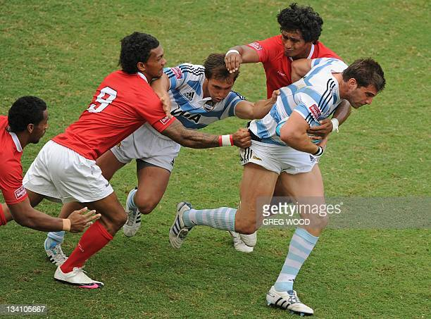 Antonio Ahualli de Chazal of Argentina attempts to break a tackle during the Rugby Sevens World Series bowl semifinal match against Tonga on...