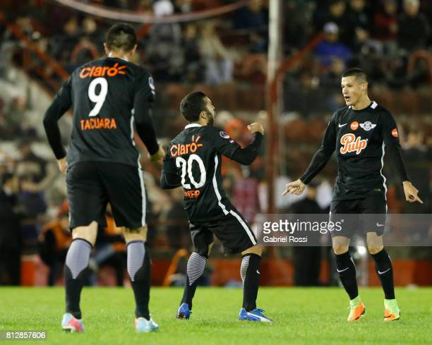 Antonio Bareiro of Libertad celebrates with teammates Oscar Cardozo and Alan Benitez after scoring the fourth goal of his team during a first leg...
