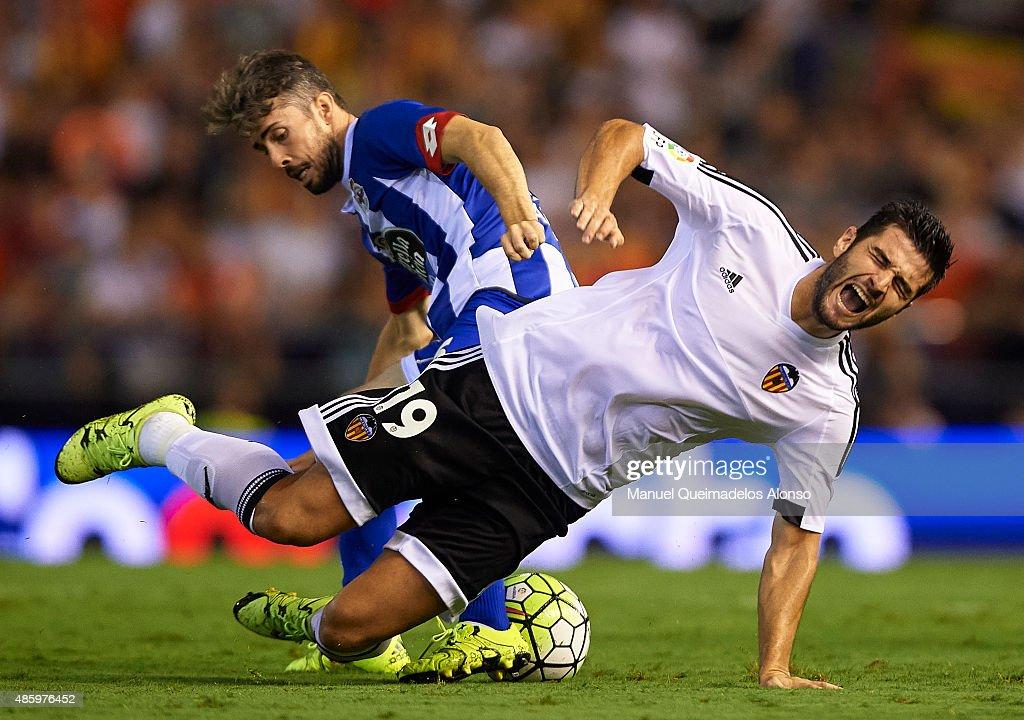 Antonio Barragan of Valencia is tackled by Luisinho Correia of Deportivo during the La Liga match between Valencia CF and RC Deportivo de La Coruna...