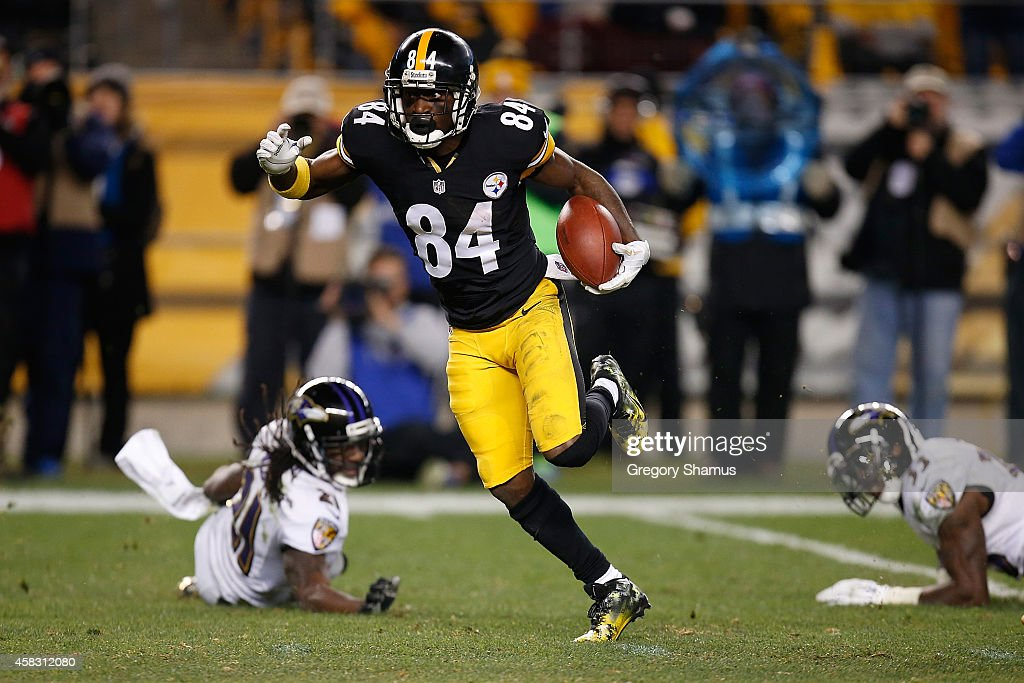 Antonio Brown #84 of the Pittsburgh Steelers avoids a tackle by Lardarius Webb #21 and Will Hill #33 of the Baltimore Ravens and scores a 54 yard touchdown during the fourth quarter at Heinz Field on November 2, 2014 in Pittsburgh, Pennsylvania.