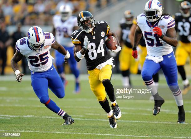 Antonio Brown of the Pittsburgh Steelers runs for a touchdown in front of Da'Norris Searcy and Brandon Spikes of the Buffalo Bills during the first...