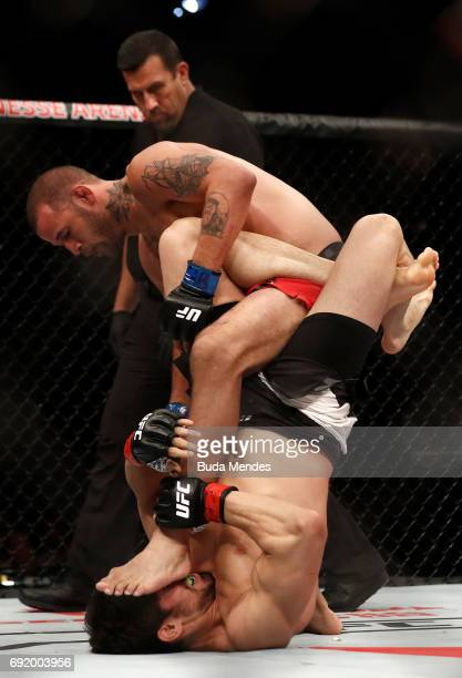 Antonio Carlos Junior of Brazil attempts to secure a leg lock submission against Eric Spicely in their middleweight bout during the UFC 212 event at...