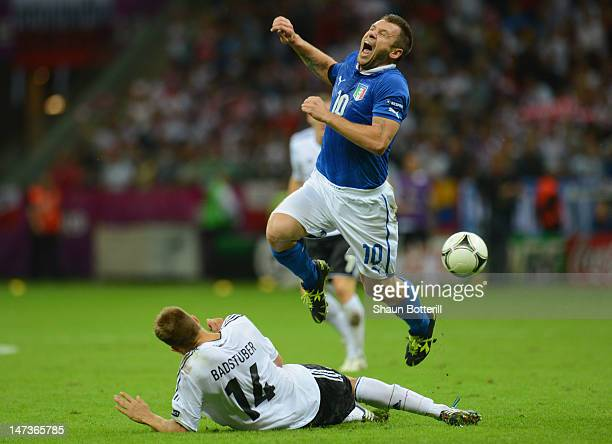 Antonio Cassano of Italy grimaces as he attempts to evade a challenge from Holger Badstuber of Germany during the UEFA EURO 2012 semi final match...