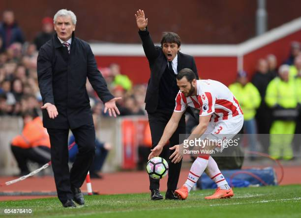 Antonio Conte manager of Chelsea and Mark Hughes manager of Stoke City react during the Premier League match between Stoke City and Chelsea at Bet365...