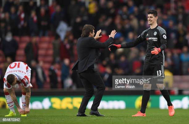 Antonio Conte manager of Chelsea celebrates victory with Thibaut Courtois of Chelsea after the Premier League match between Stoke City and Chelsea at...