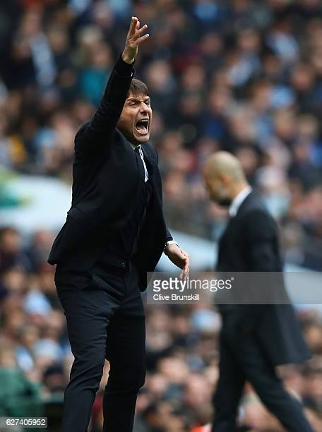 Antonio Conte Manager of Chelsea gives instructions as Josep Guardiola Manager of Manchester City shows his dejection during the Premier League match...