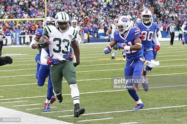 Antonio Cromartie of the New York Jets is tackled out of bounds by Corey Graham of the Buffalo Bills and Leodis McKelvin of the Buffalo Bills after a...