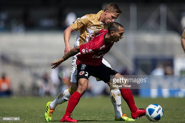 Antonio Garcia of Pumas fights for the ball with Edgar Castillo of Xolos during a match between Pumas UNAM and Tijuana as part of the Clausura 2014...